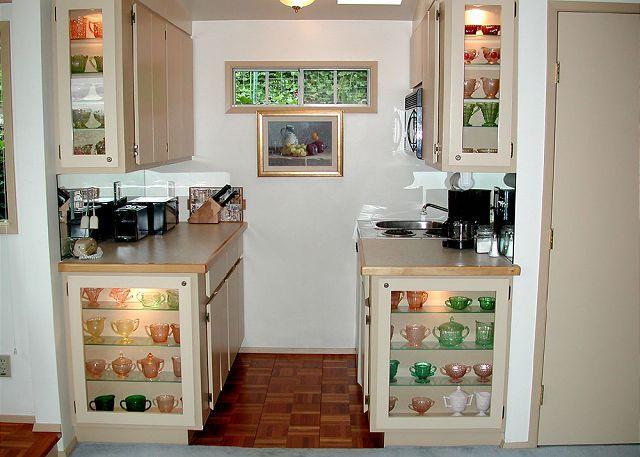 La casa de huéspedes tiene una cocina con gabinetes de conveniencia que muestran colorido cristalería.