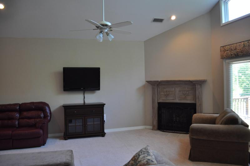 Living room with a vaulted ceiling, HDTV, fireplace, and plenty of seating