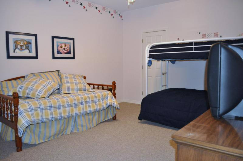 Downstairs bedroom with a twin/full bunkbed and another twin bed