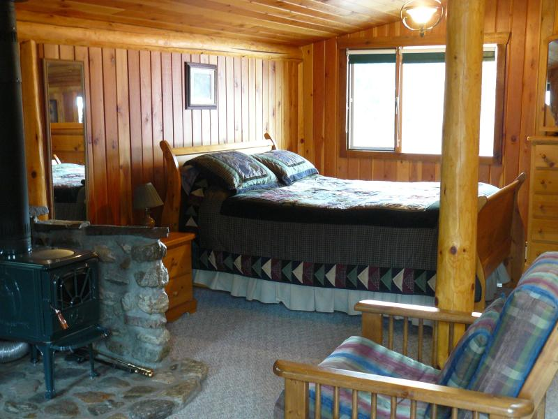 Sled queen bed close to wood stove surrounded by wood/log construction
