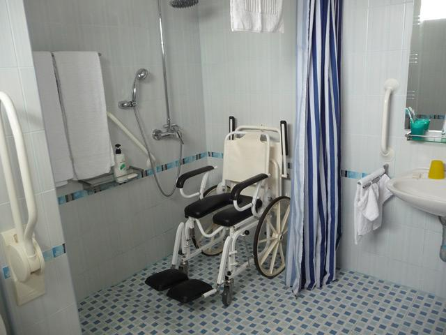 Shower wheelchair with soft padded seat and foot rests.