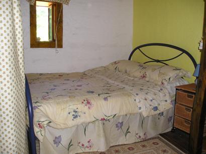 Segundo quarto com uma cama de casal e cama de solteiro, mesas de cabeceira e tapete