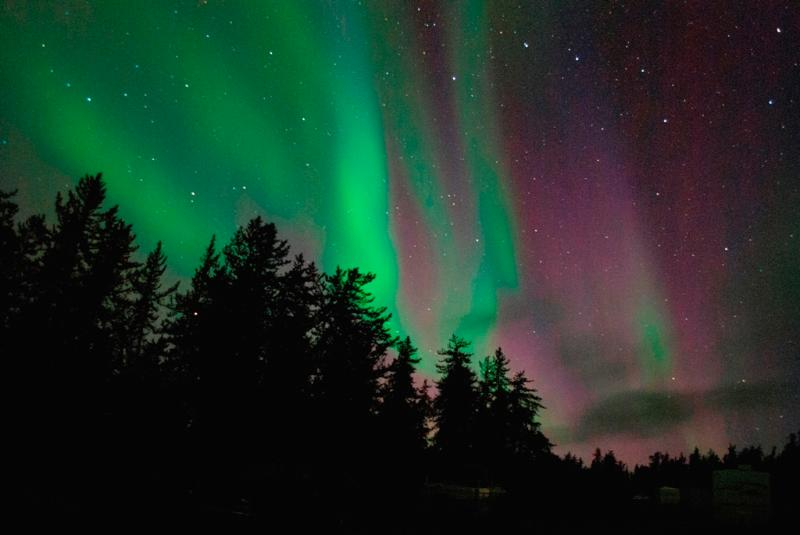 Northern Lights in front of cabins