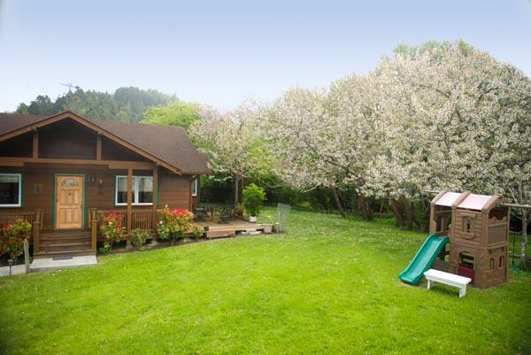 Beautiful landscaped yard includes swing set and playhouse for children.