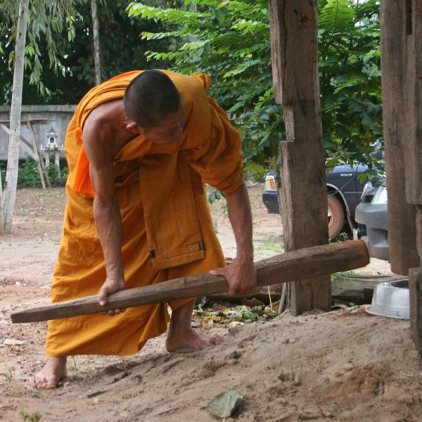 A monk sounding the gong at a wat