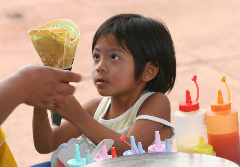 Little girl getting her pancake from a street vendor