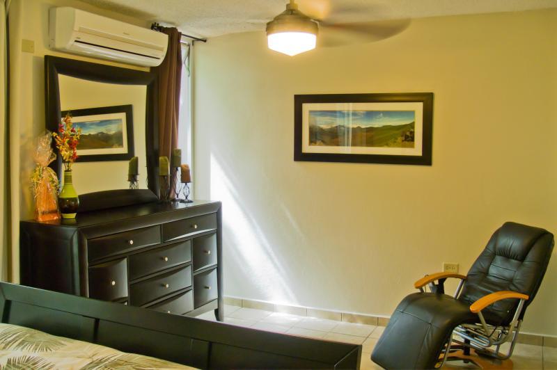 Air conditionné chambre des maîtres avec lit queen, table de nuit, la poitrine et walk-in
