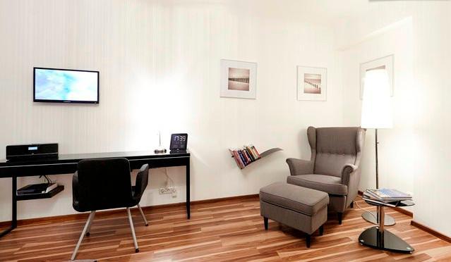 Dormitorio con asiento cómodo y mapas & cityguides...