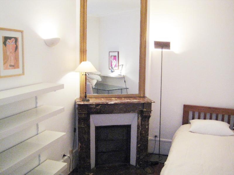 bedroom with fire place (not used) and mirror