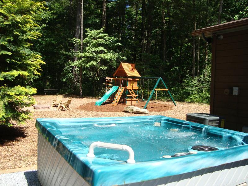 Bañera de hidromasaje privada grande justo afuera de tu puerta & Mira hacia el bosque. Juegos infantiles en fondo