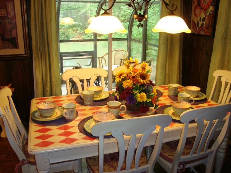 Mesa de comedor pintado a mano & sillas; servicio de mesa colorido; las puertas se abren a solarium, sala de estar