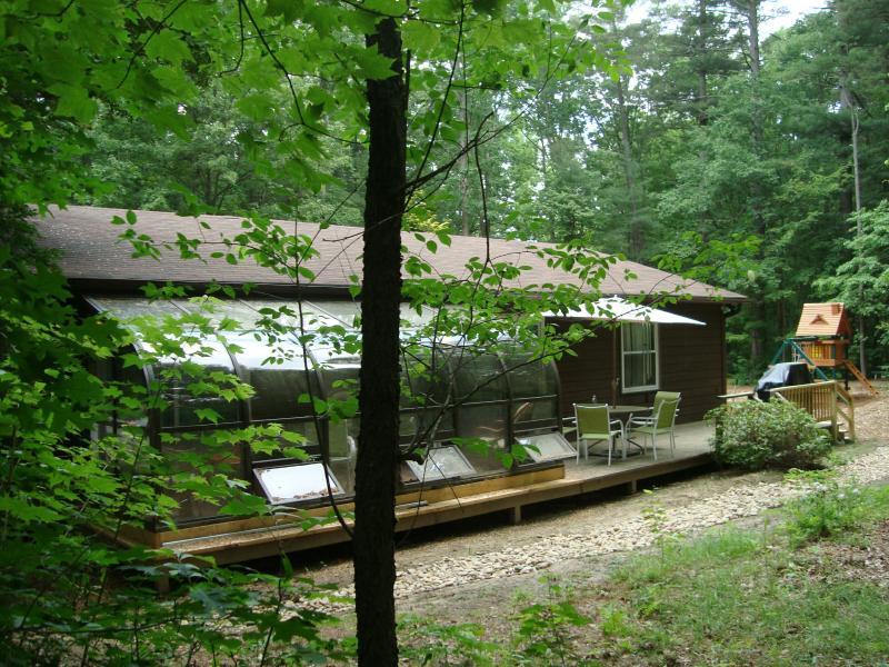Vista lateral cabaña de Stoney Creek de la zona de solarium y un patio con mesa, sillas & parrilla de gas