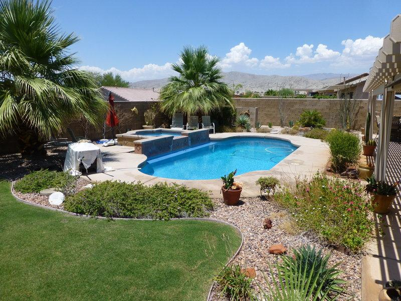 Pool/spa with waterfalls surrounded by palm trees & desertscape with mountain views
