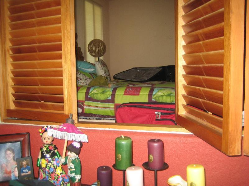bedroom shutters open into living area