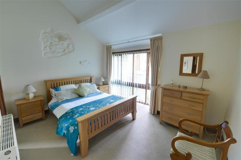 The main bedroom is spacious with a double bed, attractive furniture and pretty linens