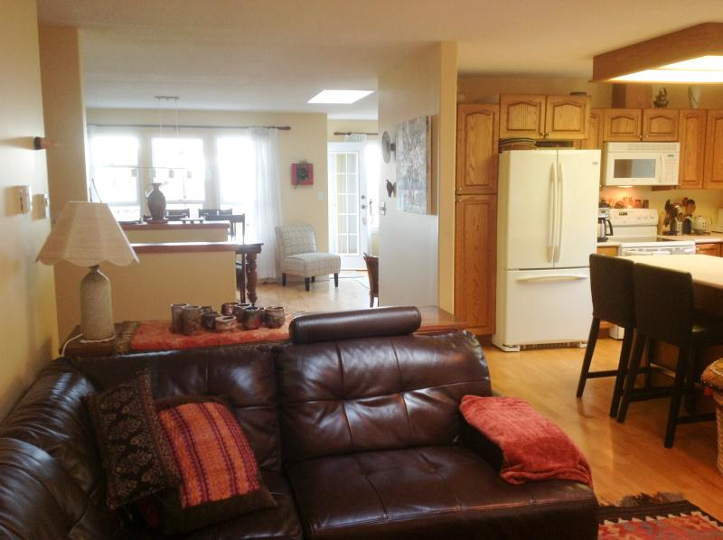 Family Room - Leather couch overlooking the garden and open concept with the kitchen.  looking to LR