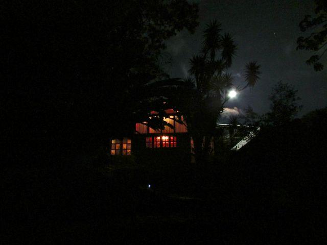 View of house at night from the garden under the full moon