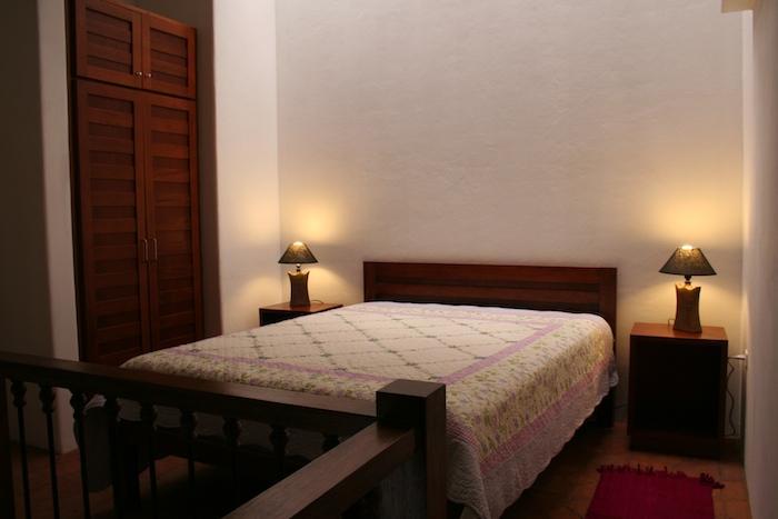 El loft dormitorio tiene una cama queen, mesas, lámparas y un amplio armario.