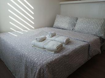 Queen size bed with newly washed sheets and towels