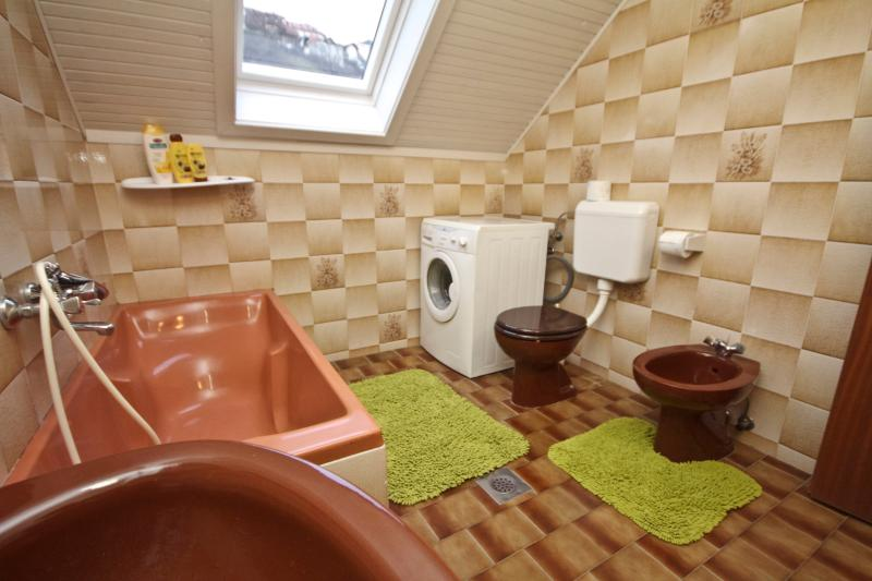 Bathroom with a washer and a view of old town.