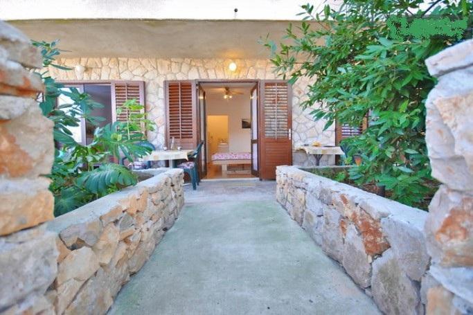 entrada do apartamento entre 2 pequenos jardins com palmeiras, mesa com cadeiras na frente