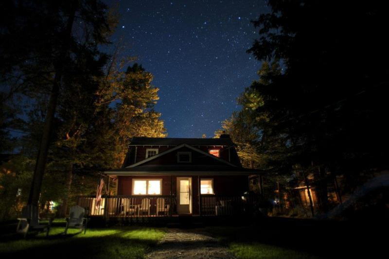 Parte traseira do chalé à noite, olhando para as estrelas