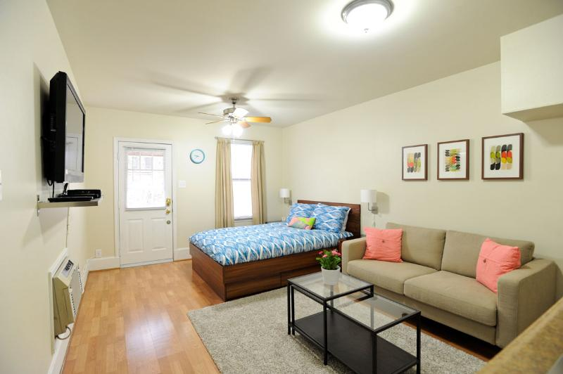 Open floor plan with queen bed, couch, and large 42 inch flat screen tv.