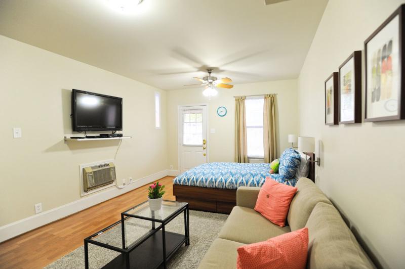 Plan d'étage ouvert avec lit queen, divan et grand plat de 42 pouces écran tv.