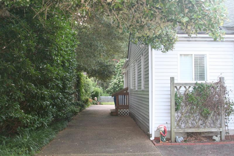 Shady driveway with side entrance to house.
