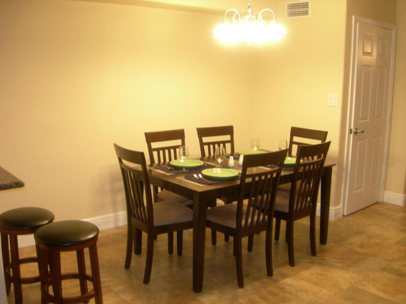 Dining room, large table, six comfy chairs and two stools.