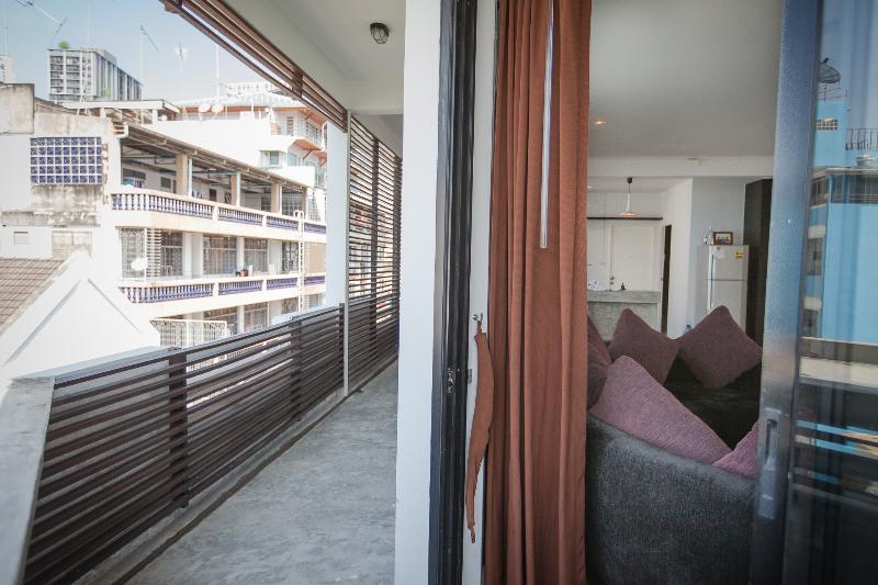 Grand balcon juste à l'extérieur du salon avec verre les murs entre les deux.