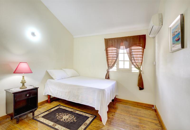 Warmly furnished master bedroom with double bed and A/C unit.