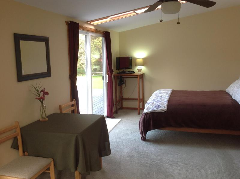 Spacious bedroom with a queen bed overlooking a beautiful lily pond