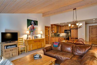Living room with gas fireplace, flat screen television, and dining area with seating for 6.