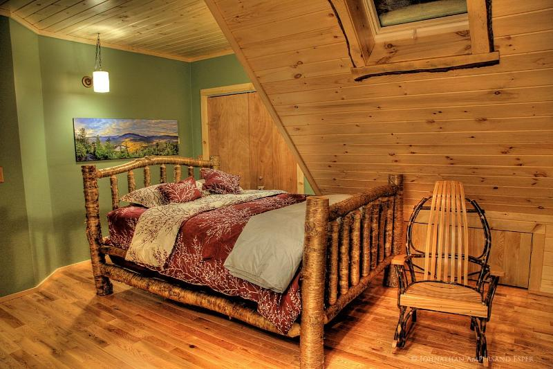 Master bedroom with yellow birch queen bed and hickory rocker