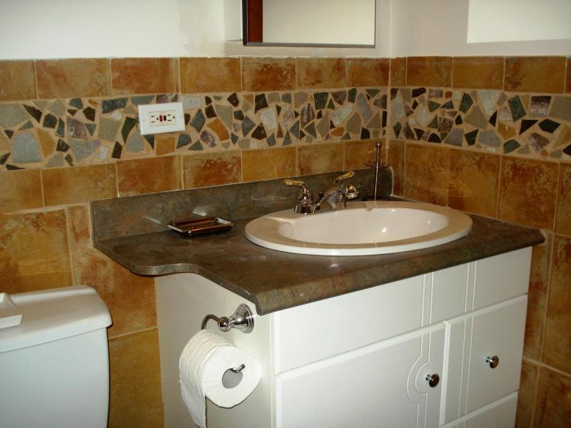 The bathroom has a unique hand crafted tile design on the wall and floor.