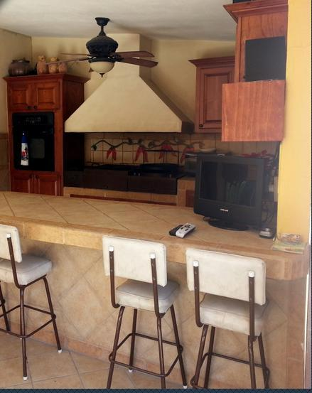 Outdoor patio and grill will the bar seating area