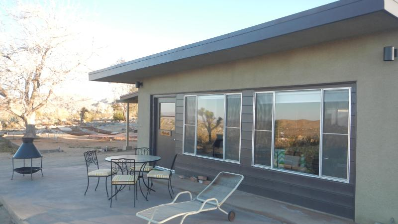 Outdoor dining table and firepit on private north-facing patio overlooking 20+ acres of open desert.