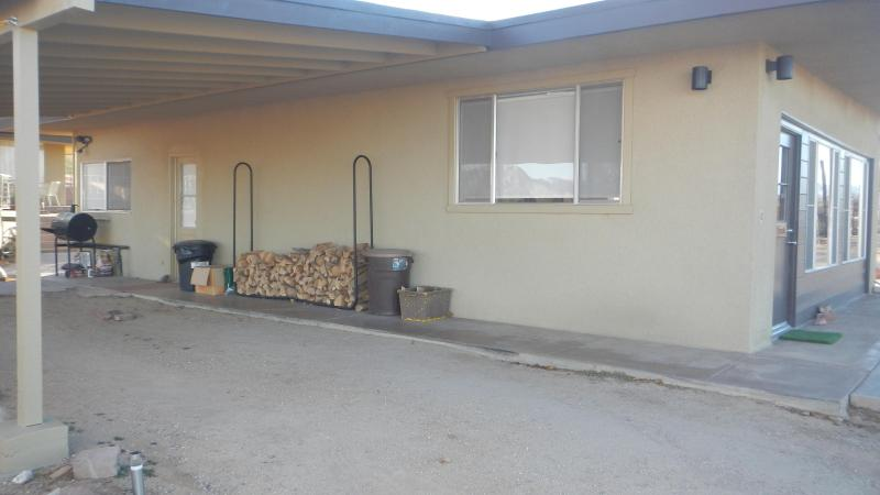 Charcoal grill and firewood under carport.