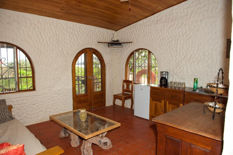 Livingroom and kitchen area with views of the ocean and garden folage