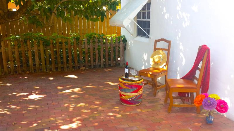Cottage front patio covered by avocado tree