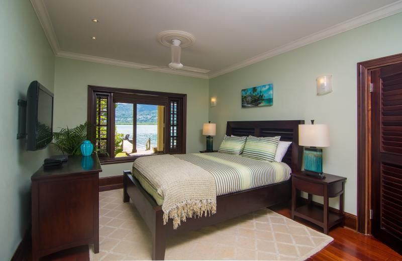 Bedroom number 4, downstairs, with tv and queen bed and gorgeous view to the lagoon