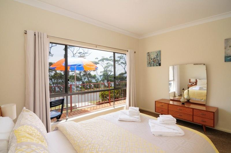 Upstairs master bedroom featuring double bed and stunning views of Jervis Bay