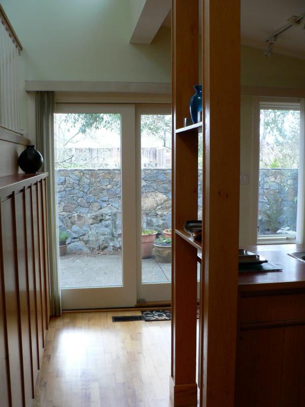 De ommuurde patio van graniet lonkt naar beneden de centrale hal langs de rode keuken.