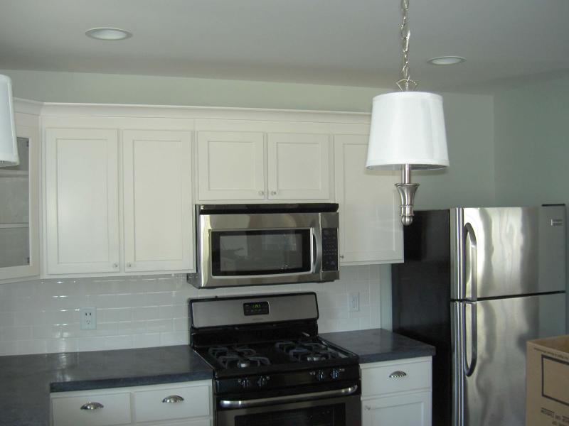 Cozinha conceito aberto com utensílios de aço inoxidável e bancadas concretas. Pisos de tábua de pinho.