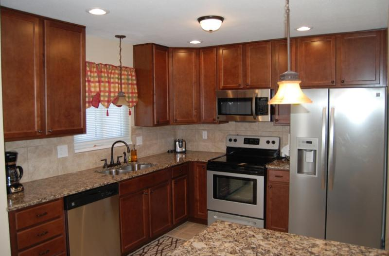 Updated kitchen with granite counters, tile backsplash, and stainless steel appliances