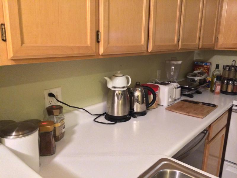 full kitchen with oven, sink, refrigerator, microwave, coffee maker, toaster, blender, and many more