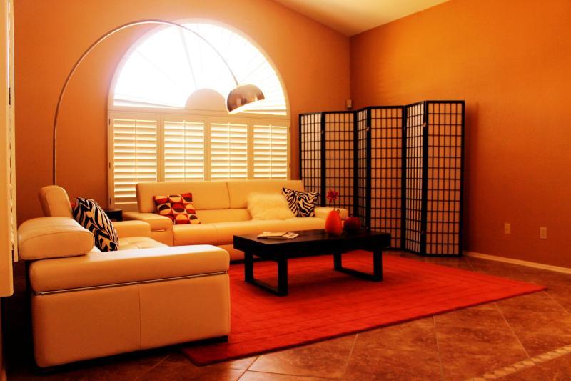 Sala eclética com Natuzzi sofás de couro, uma lâmpada de arco legal e tela de zen