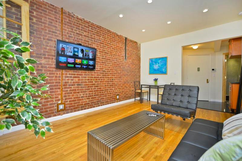 Woonkamer, flatscreen TV op originele bakstenen muur, eigentijds meubilair
