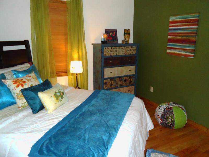 En un dormitorio de tamaño king ambient, cómodos muebles pintados a mano